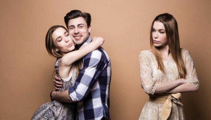 Парень обнимает другую девушку