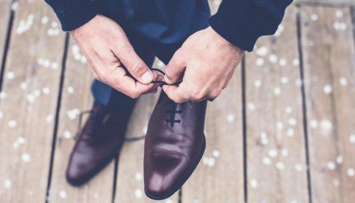 Парень завязывает шнурки