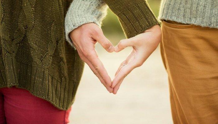 Пара делает сердечко руками