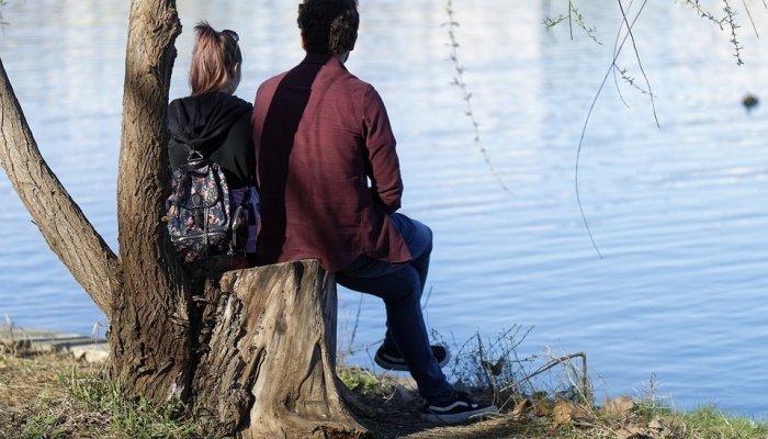 Парень и девушка отдыхают около реки